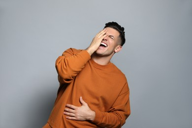 Handsome man laughing on grey background. Funny joke