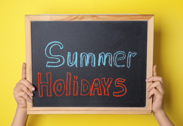 Schoolgirl holding blackboard with text SUMMER HOLIDAYS on yellow background, closeup