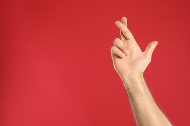 Man with crossed fingers and space for text on red background, closeup. Superstition concept