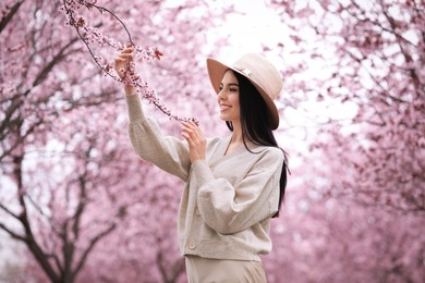 Pretty young woman in park with blooming trees. Spring look