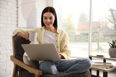 Beautiful young woman with cup of drink using laptop at home