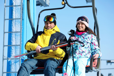 People using chairlift at mountain ski resort. Winter vacation