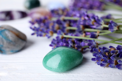 Gemstones and healing herbs on white wooden table, closeup