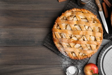 Delicious traditional apple pie on wooden table, flat lay. Space for text