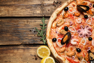 Delicious seafood pizza on wooden table, flat lay