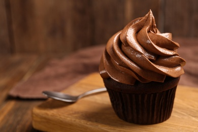 Delicious chocolate cupcake with cream on wooden table, closeup
