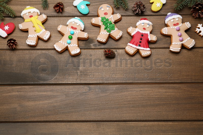 Delicious Christmas cookies and pine cones on wooden table, flat lay. Space for text