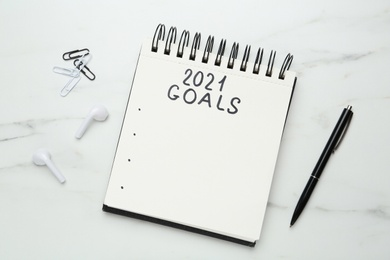 Notebook with inscription 2021 Goals, new year aims. Objects on white marble table, flat lay