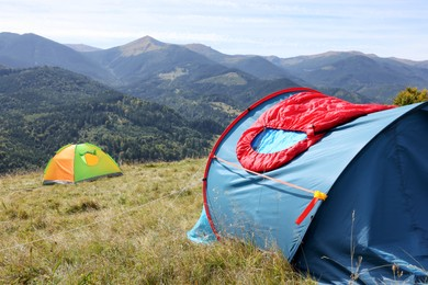 Red sleeping bag on camping tent in mountains