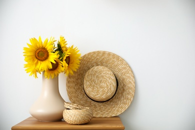 Bouquet of beautiful sunflowers, wicker basket and hat on table indoors