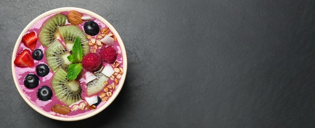 Delicious acai smoothie with granola and fruits in dessert bowl on black table, top view. Space for text