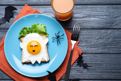 Halloween themed breakfast served on black wooden table, flat lay. Tasty toast with fried egg in shape of ghost