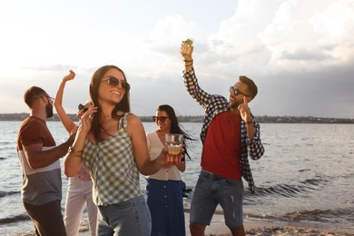 Woman with friends having fun near river at summer party