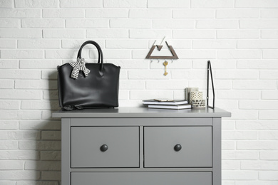 Grey chest of drawers with bag, books and decor elements near white brick wall