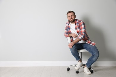 Young man sitting in comfortable office chair near white wall indoors, space for text