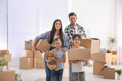 Happy family in room with cardboard boxes on moving day