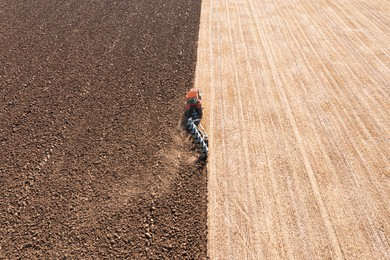 Tractor pulling plow in agricultural field on sunny day, aerial view