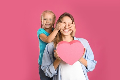 Little daughter congratulating her mom on pink background. Happy Mother's Day