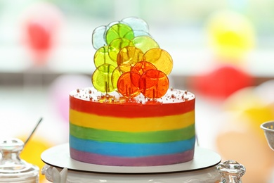 Bright birthday cake on table in decorated room