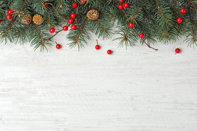 Flat lay composition with fir branches and berries on white wooden background, space for text. Winter holidays