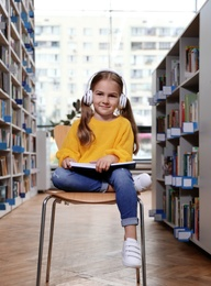 Cute little girl with headphones reading book on chair in library