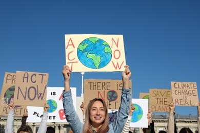 Group of people with posters protesting against climate change outdoors