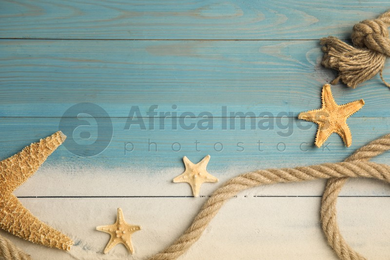Beautiful sea stars, rope and sand on light blue wooden background, flat lay. Space for text