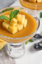 Delicious panna cotta with mango coulis and fresh fruit pieces on table, closeup