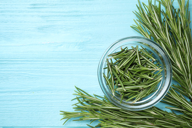 Green rosemary on light blue wooden table, top view with space for text. Healing herb