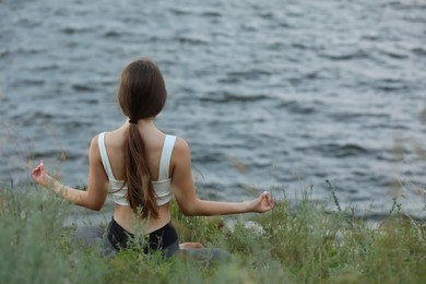 Teenage girl meditating near river, back view. Space for text