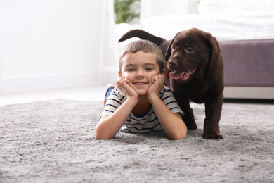 Little boy with puppy on floor in bedroom. Friendly dog