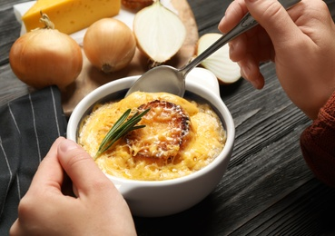 Woman eating tasty homemade french onion soup at black wooden table, closeup