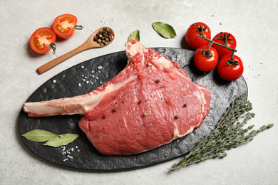 Raw rib with herbs, spices and tomatoes on grey table, flat lay