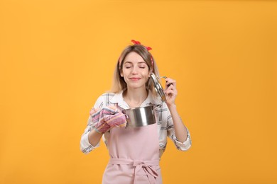 Young housewife with pot on yellow background