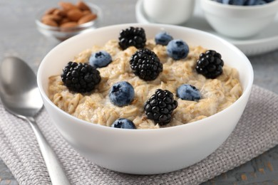 Tasty oatmeal porridge with blackberries and blueberries in bowl on table, closeup