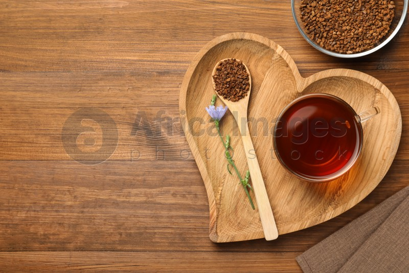 Cup of delicious chicory drink, granules and flower on wooden table, flat lay. Space for text