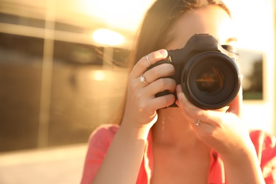 Young photographer taking picture with professional camera outdoors, closeup