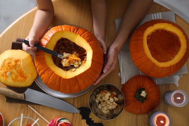 Mother and daughter making pumpkin jack o'lantern at wooden table, top view. Halloween celebration