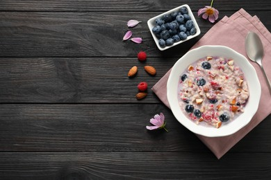 Tasty oatmeal porridge with toppings on black wooden table, flat lay. Space for text