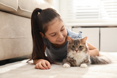 Cute little girl with cat lying on carpet at home. First pet