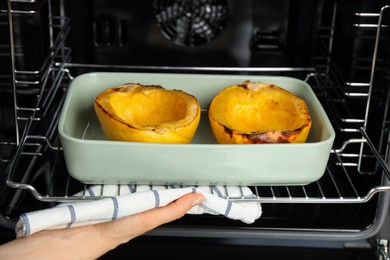 Woman taking baked spaghetti squash out of oven, closeup