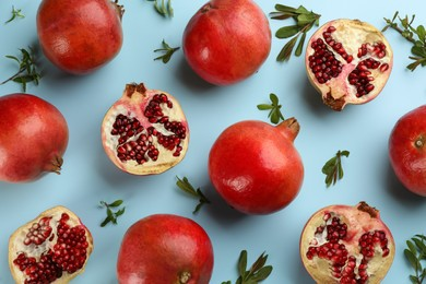 Flat lay composition with ripe pomegranates on light blue background