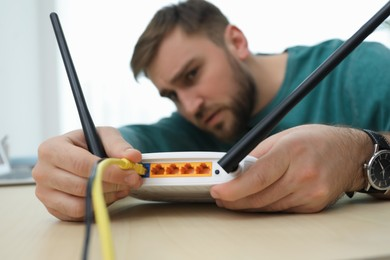 Man connecting cable to router at wooden table, focus on hand. Wireless internet communication