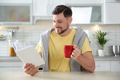 Handsome man with cup of coffee reading book at table in kitchen