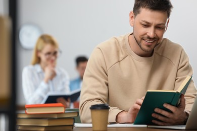 Man reading book at table in library