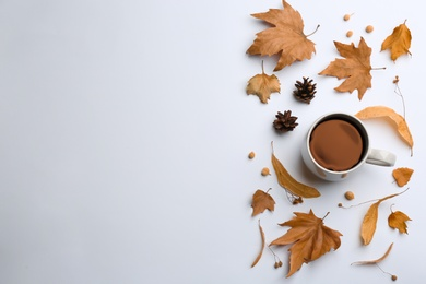 Flat lay composition with cup of hot drink and autumn leaves on white background, space for text. Cozy atmosphere