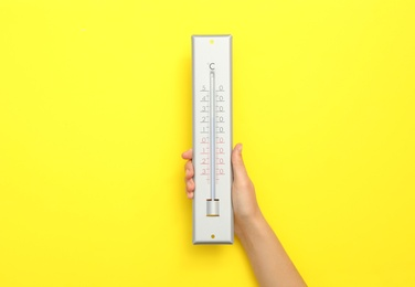 Woman with weather thermometer on yellow background, closeup