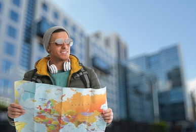 Happy traveler with map in foreign city. Vacation trip