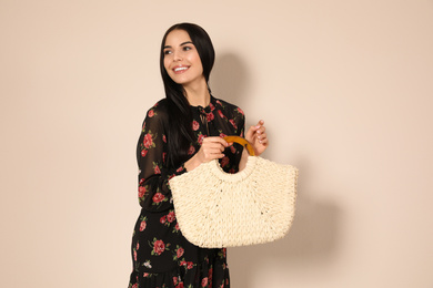 Young woman wearing floral print dress with straw bag on beige background