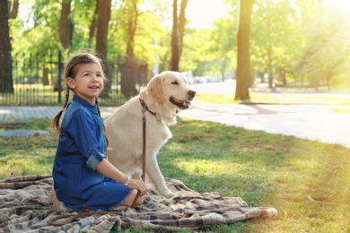 Cute little child with his pet in green park